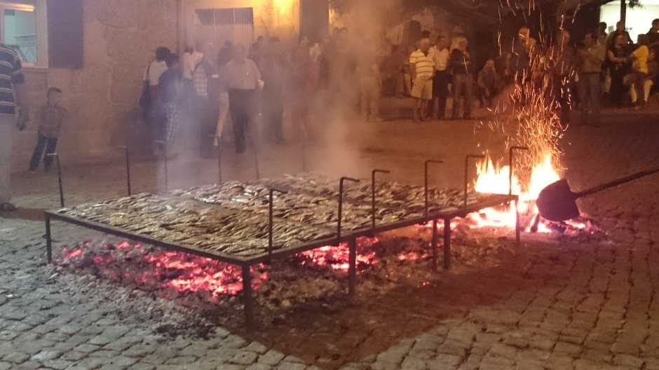 Sardines being grilled over an open fire in a town square in Portugal.