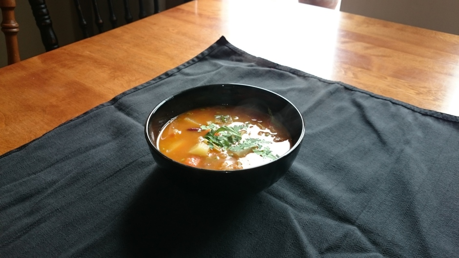 Bowl of steaming summer soup topped with cilantro in natural light.