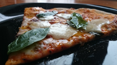 Slice of Margherita pizza fresh out of the oven