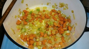 Carrots, onion, and celery cooking in a dutch oven.